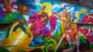 Anieken Udofia mural of diverse group of children watering garden together