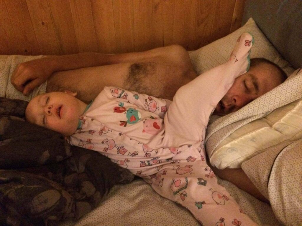 Young child asleep in starfish position with foot on dad's head