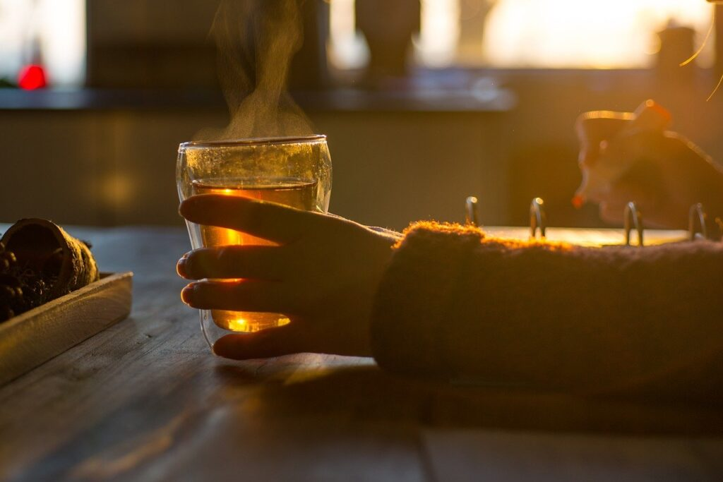 Steaming hot cup of tea in woman's hands with soft light streaming through window