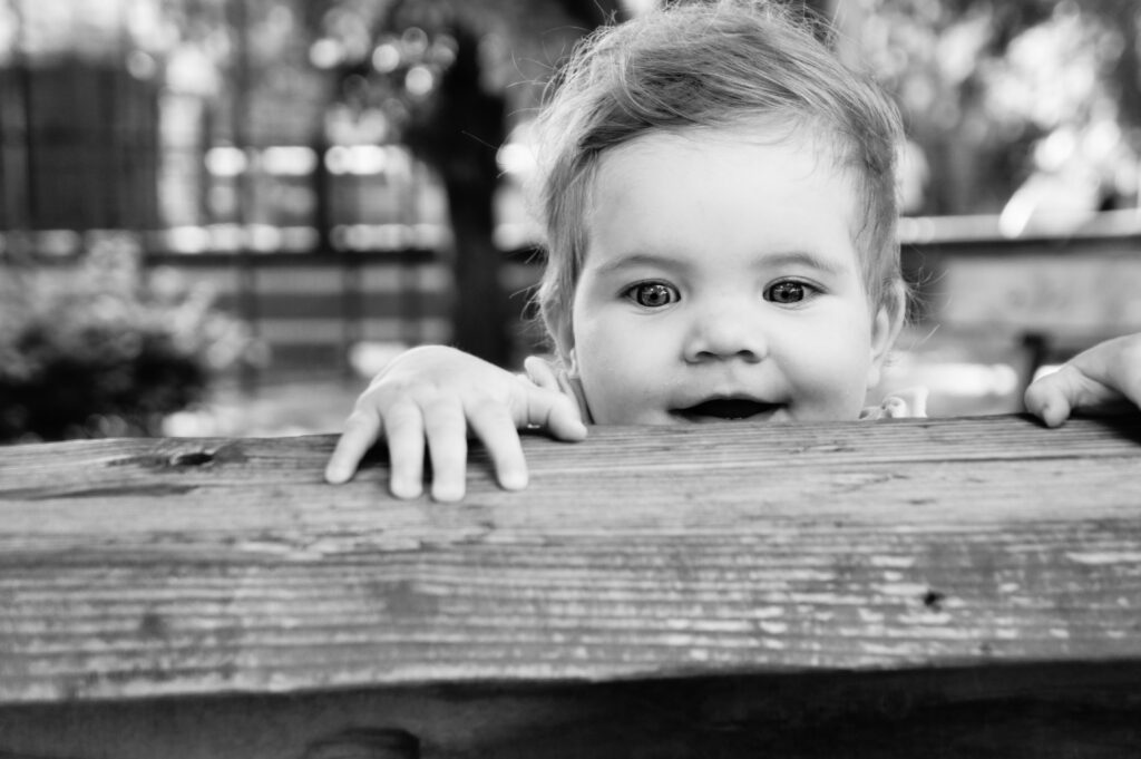 Curious toddler peering over wooden ledge with look of amazement on her face, black and white photo