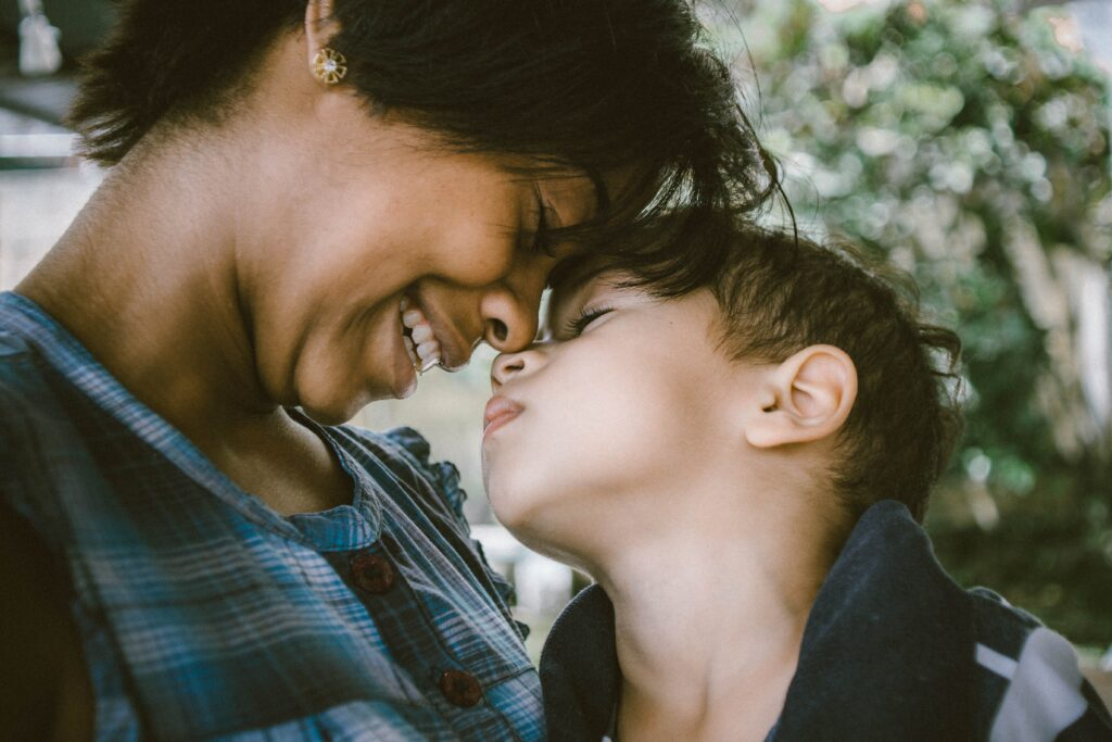 Smiling mother and elementary aged son touch foreheads
