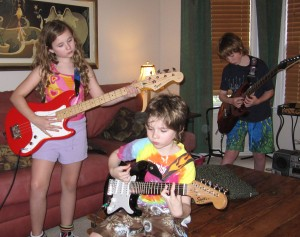 My kids, attached to each other ... and their guitars.
